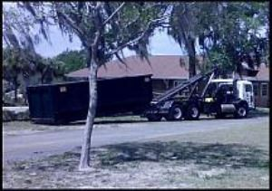 White semi truck dropping off black construction container in front of house